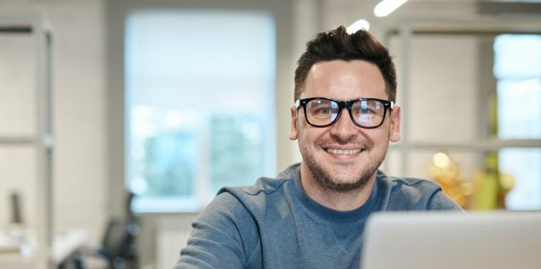 Man met bril achter laptop doet online scholing