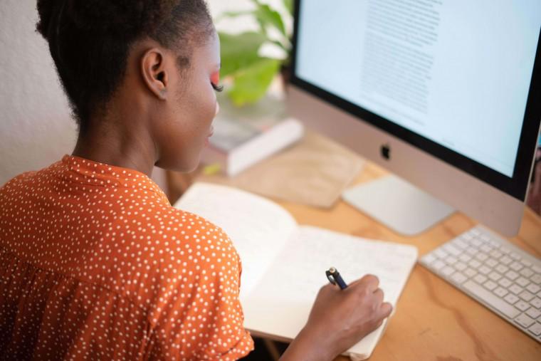 Vrouw schrijft in haar notitieboekje.